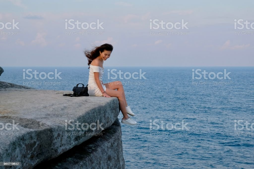 Chinese girl on cliff edge against ocean. royalty-free stock photo