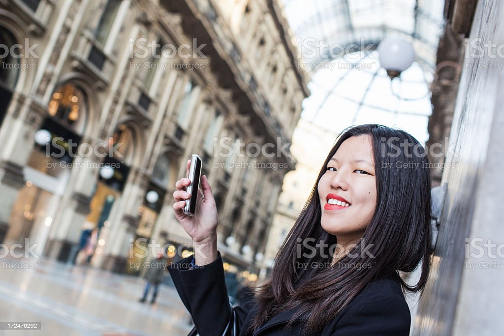 Chinese girl on the phone in Piazza Duomo, Milan, Italy royalty-free stock photo