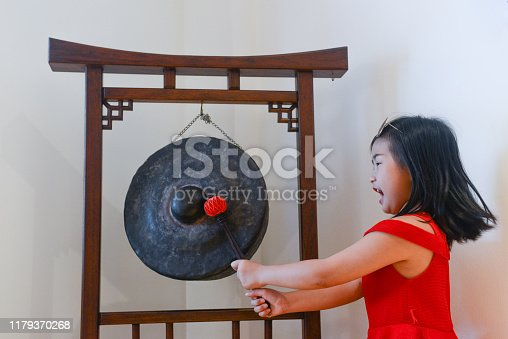Chinese girl plays the gong during Chinese New Year