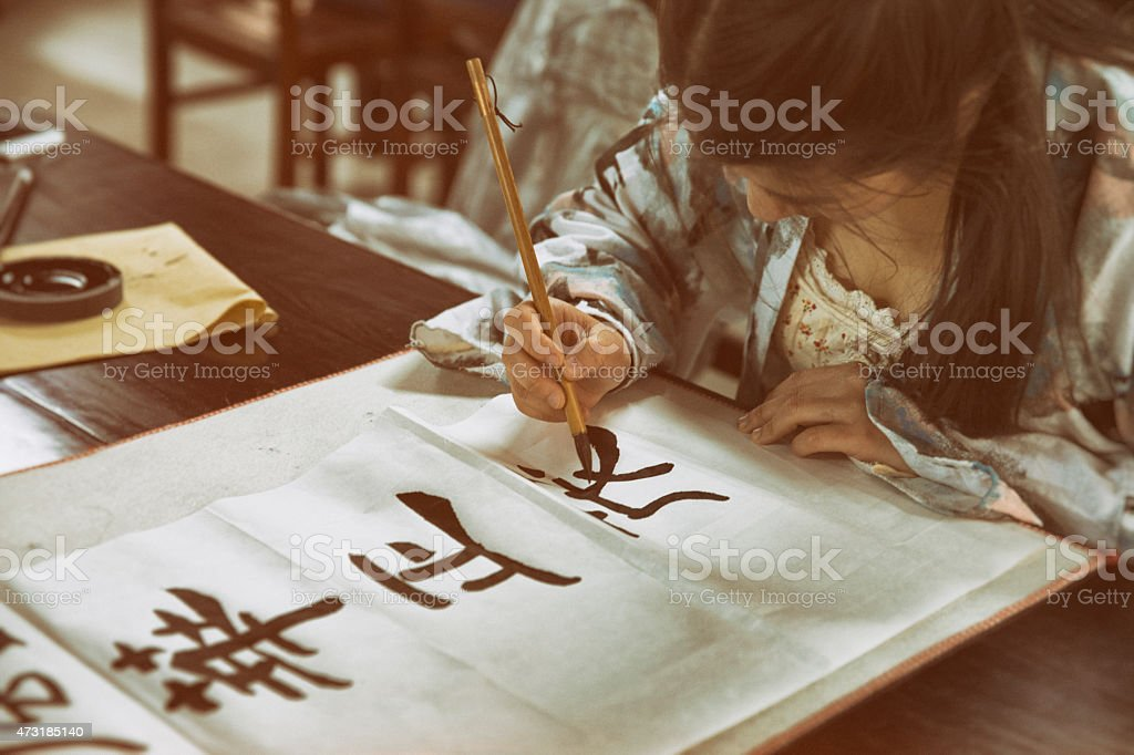 Chinese girl practising calligraphy stock photo