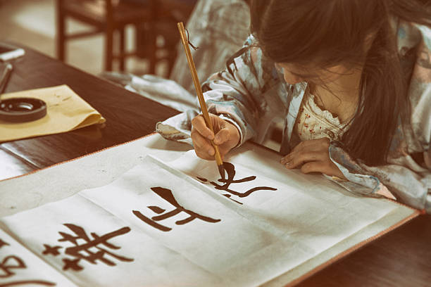 chinese girl practising calligraphy - calligraphy stock photos and pictures