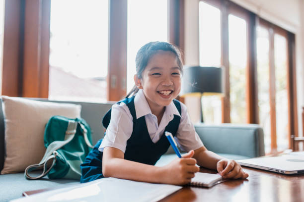 chinese girl smiling and doing homework - girl study home laptop front imagens e fotografias de stock