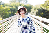 chinese girl with a sun hat, happy walking on the pedestrian bridge