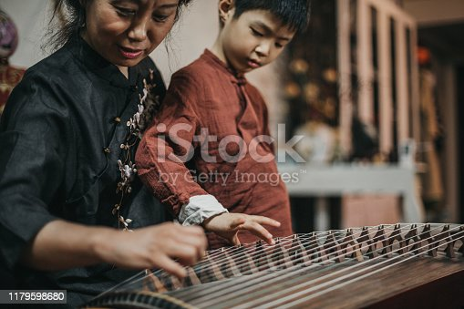 Chinese grandmother and grandson in traditional clothes playing harp