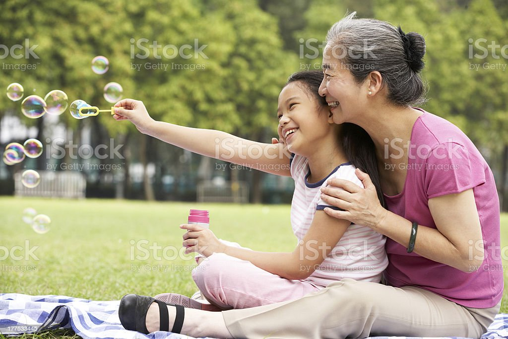 Chinese Grandmother With Granddaughter In Park Blowing Bubbles stock photo
