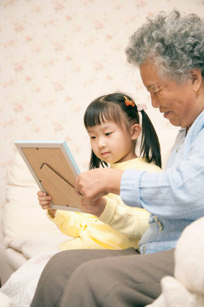 Chinese grandmother with granddaughter looking at framed photo stock photo