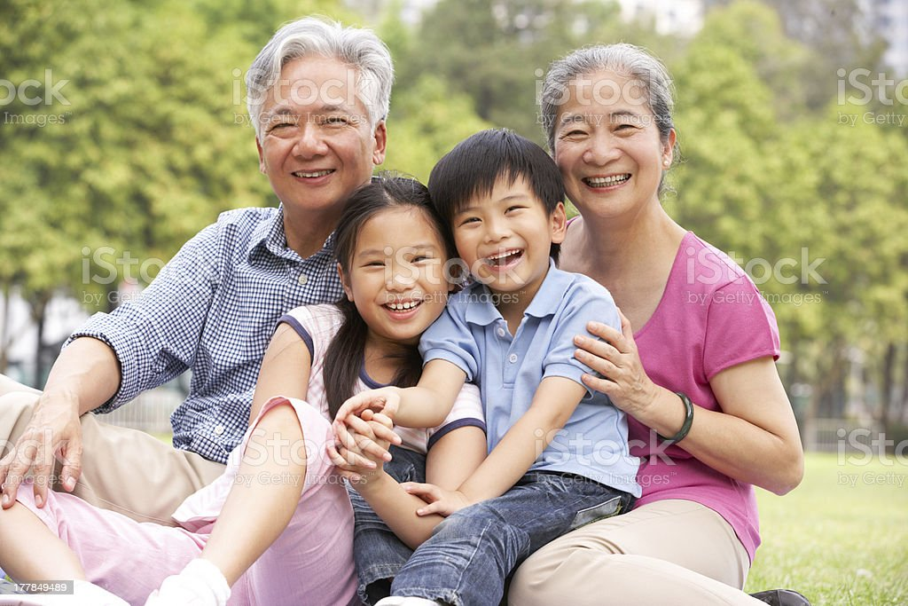 Chinese Grandparents Sitting With Grandchildren In Park stock photo