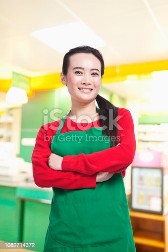 istock Chinese grocery store worker in apron with arms crossed 1082714372