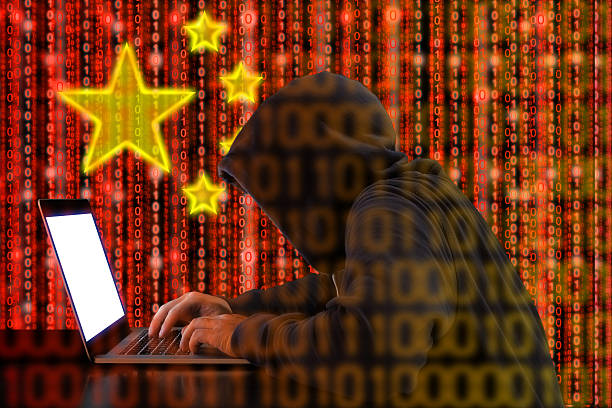 Chinese hacker at work in front of red flag stock photo