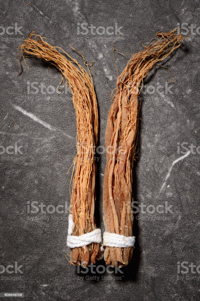 Chinese herbal medicines -- ginseng rootlets on stone background stock photo