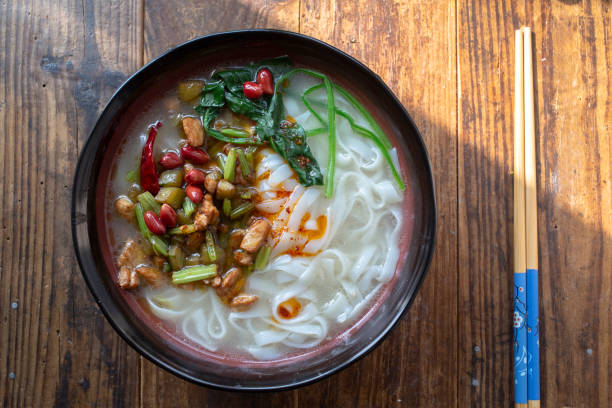 Chinese homemade rice noodles: with broth, chicken meat,spinach and celery stock photo