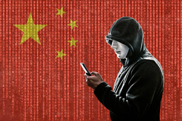 Chinese hooded hacker with mask holding smartphone stock photo