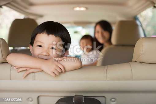 istock Chinese kid sitting in backseat of car 1083127098