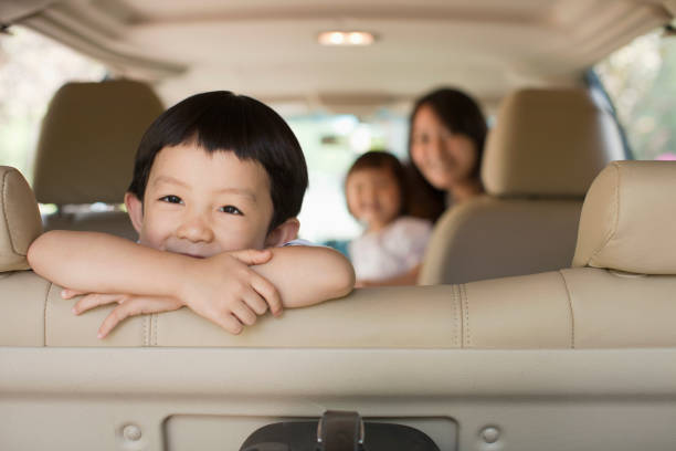 Chinese kid sitting in backseat of car stock photo