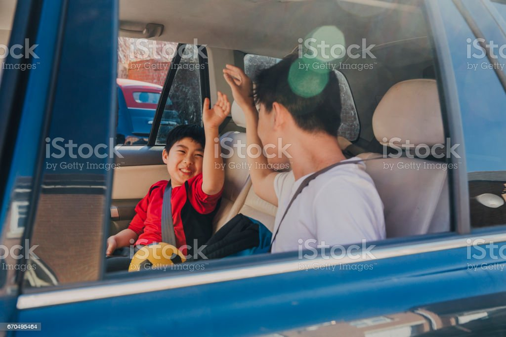 Chinese Kids Laughing in Backseat stock photo