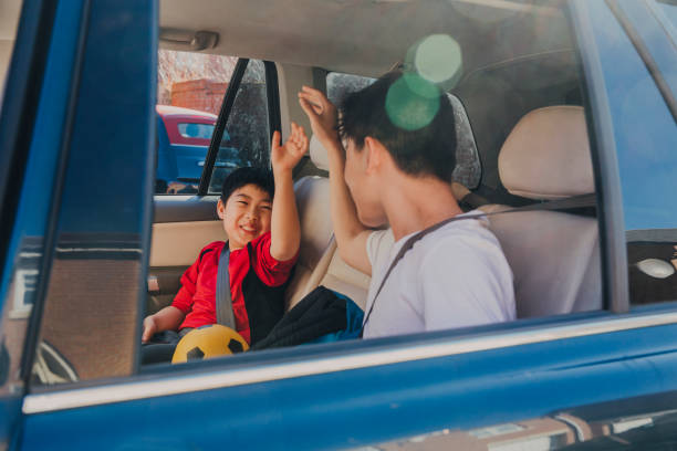 Chinese Kids Laughing in Backseat stock photo