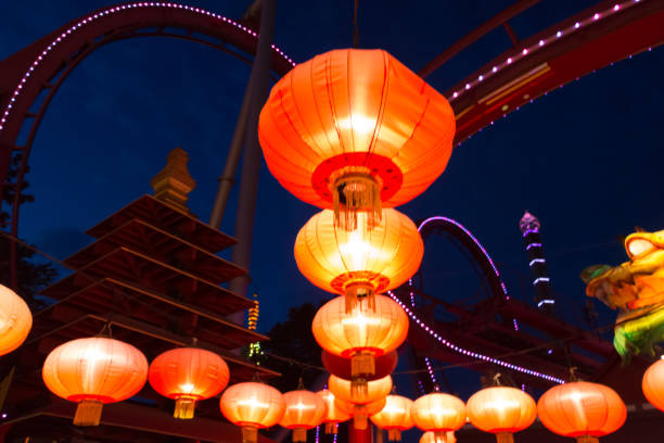 Chinese lanterns lit at an amusement park at night with a pagoda and a roller coaster in the background stock photo