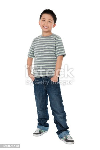 Full length of Chinese little boy smiling with hands in pockets over white background. Vertical Shot.