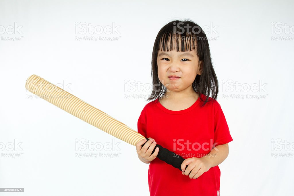 Chinese little girl holding baseball bat with angry expression stock photo