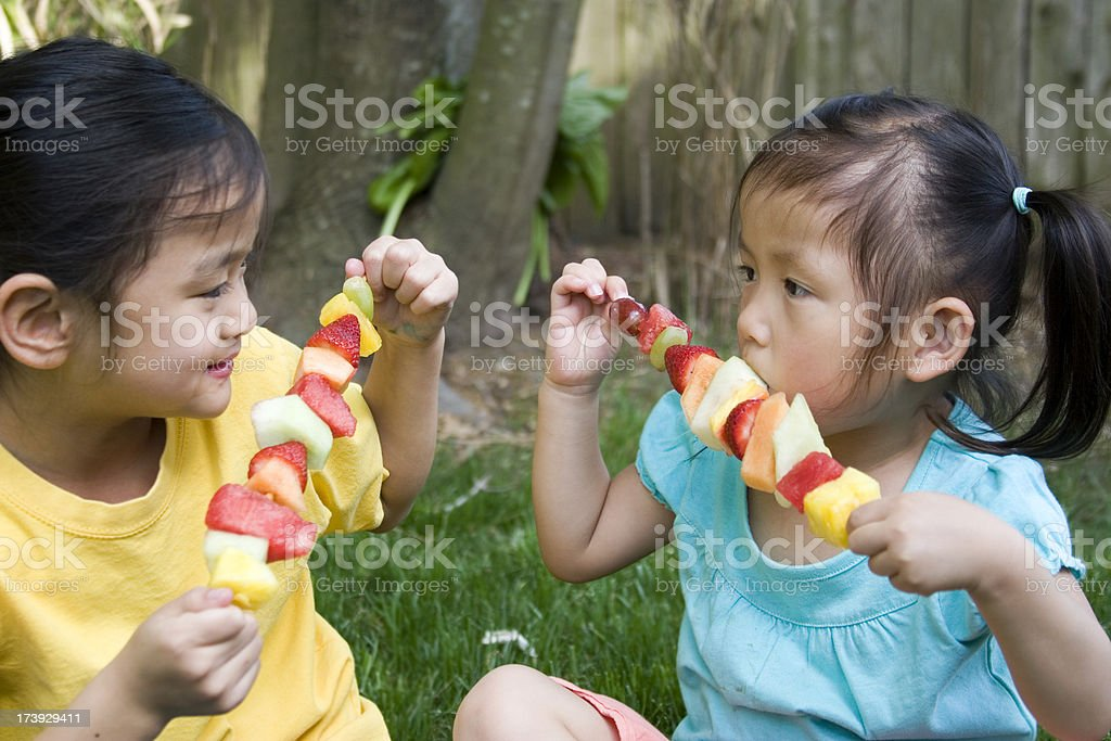 Chinese little girls eating a variety of fruit royalty-free stock photo