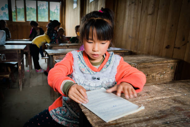 Chinese little school girl learning to write in old chinese classroom stock photo