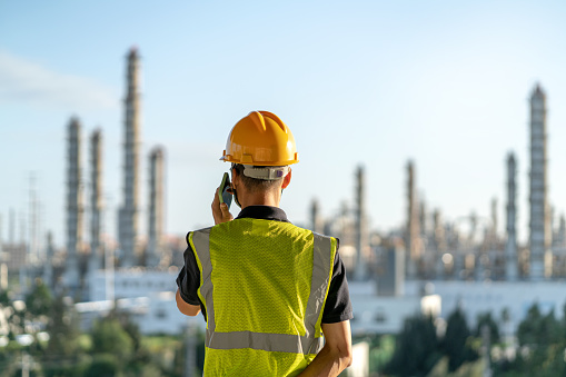 Chinese male engineer on the phone in chemical plant