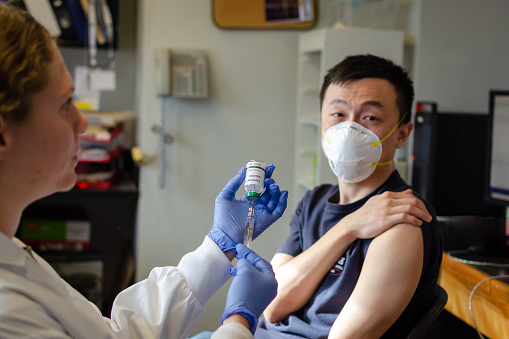 Chinese Male Receiving Coronavirus Vaccine In Clinic Stock Photo - Download Image Now