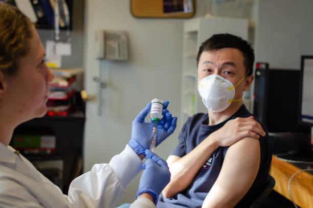 Chinese male receiving coronavirus vaccine in clinic Illustrative picture of Chinese male getting vaccinated against coronavirus middle east respiratory syndrome stock pictures, royalty-free photos & images