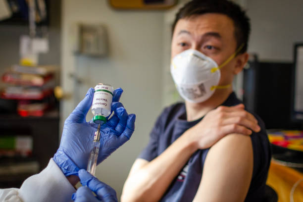 Chinese male receiving coronavirus vaccine in clinic Illustrative picture of Chinese male getting vaccinated against coronavirus vaccine stock pictures, royalty-free photos & images