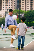 A Chinese man and boy play by a soccer field in Hong Kong.