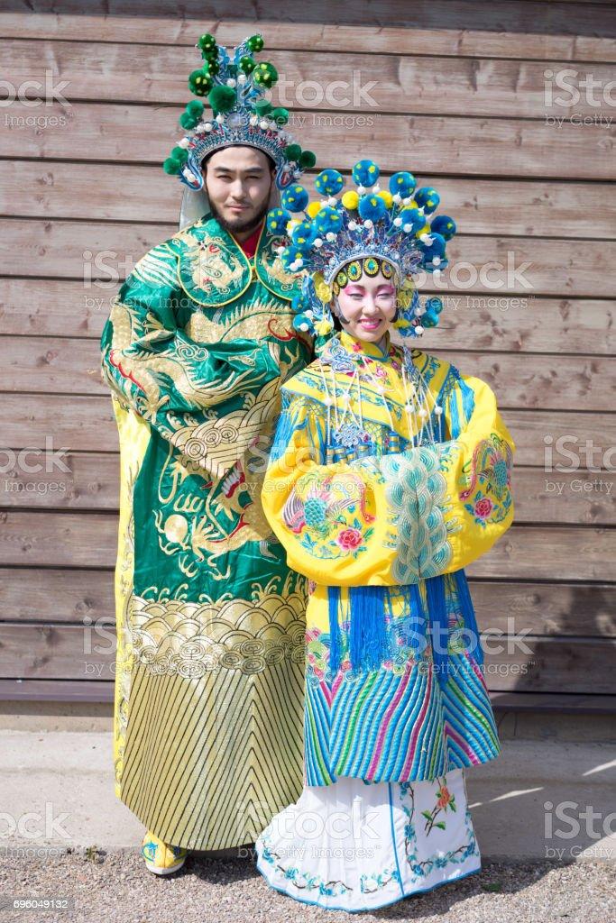 a1c7c41ebe3255 Chinese man en vrouw in klederdracht permanent in de buurt van de houten  wand royalty free