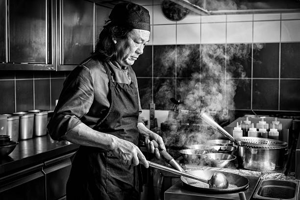 chinese man cooking in asian restaurant serious chinese man cooking in the kitchen of an asian restaurant cooking black and white stock pictures, royalty-free photos & images