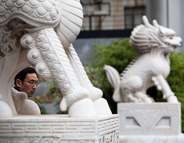 Chinese man next to Imperial Lion stock photo