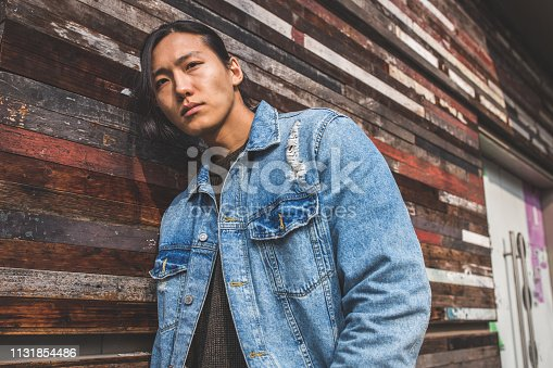 Handsome Asian man with long hair and denim jacket  portrait