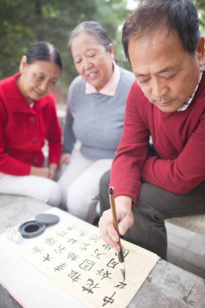 chinesischer mann üben kalligraphie im park - gedichte zum ruhestand stock-fotos und bilder