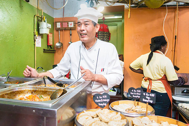 Chinese man serving food at the market in Hout Bay Cape Town, South Africa - November, 23rd 2014: Chinese chef serving chinese food at the Hout Bay Market, happy and smiling with his speciality food seen on display. His assistant seen frying in the background. hout stock pictures, royalty-free photos & images