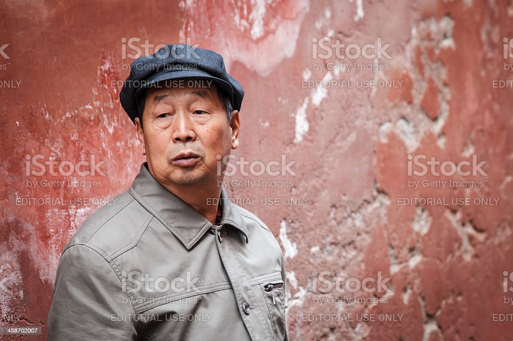 Chinese man standing in front of the red wall stock photo