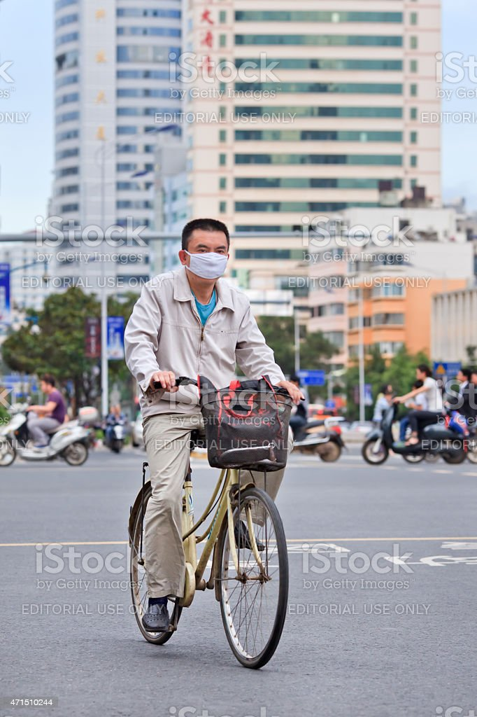 Chinese man with mouth cap on a bicycle, Kunming, China stock photo