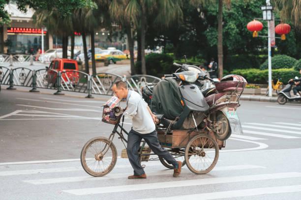 Chinesischer Mann mit Dreirad mit zwei alten Roller beladen – Foto