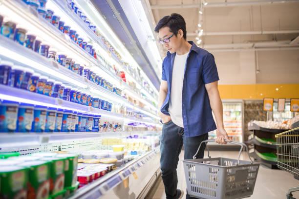 một người đàn ông trưởng thành trung quốc cầm giỏ và duyệt tìm các sản phẩm trong bộ phận hàng đông lạnh. - yogurt hình ảnh sẵn có, bức ảnh & hình ảnh trả phí bản quyền một lần