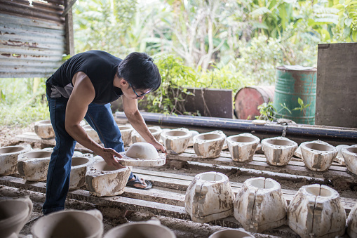 Chinese mature man isolating ceramic from mold in his workshop