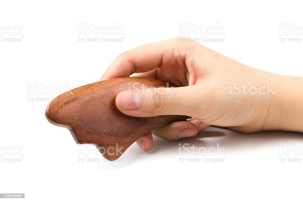 Chinese medical tool Guasha made from hardwood with hand isolate stock photo