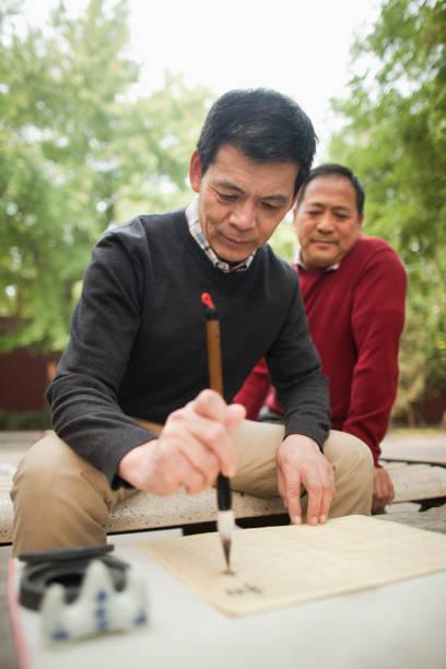 chinesische männer üben kalligraphie im park - gedichte zum ruhestand stock-fotos und bilder