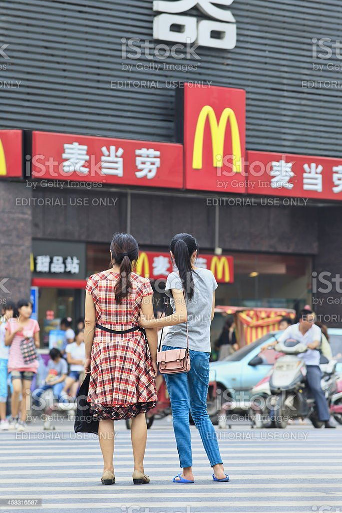 Chinese Mom and daughter in front of MacDonals outlet stock photo