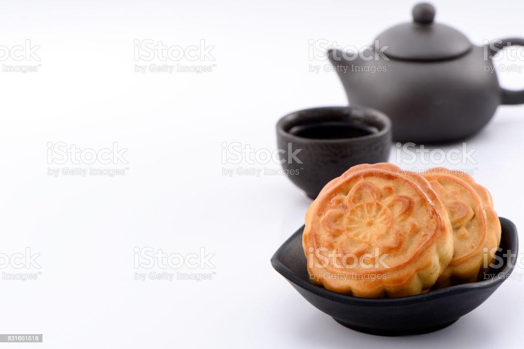 chinese moon cake -- food for Chinese mid-autumn festival on   a black bowl with tea cup and teapot isolated on white   background stock photo