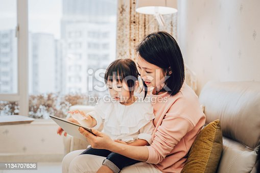 Chinese mother and daughter using digital tablet