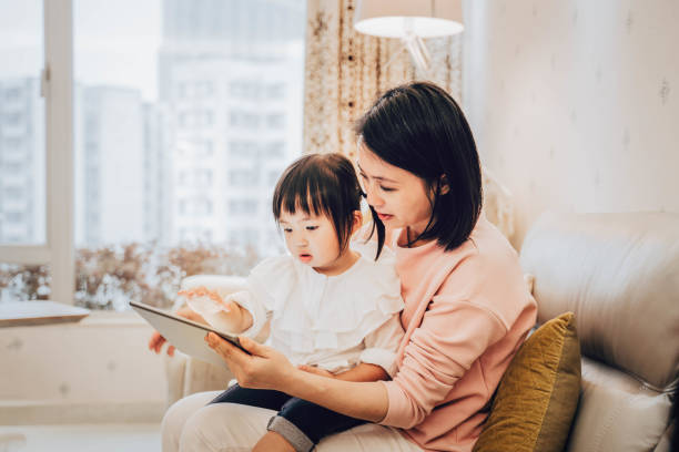 chinese mother and daughter using digital tablet - cultura cinese foto e immagini stock