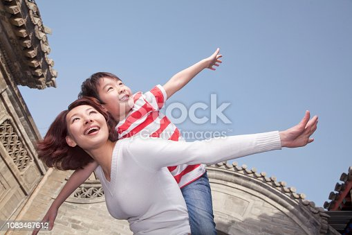 Chinese mother giving son piggyback ride