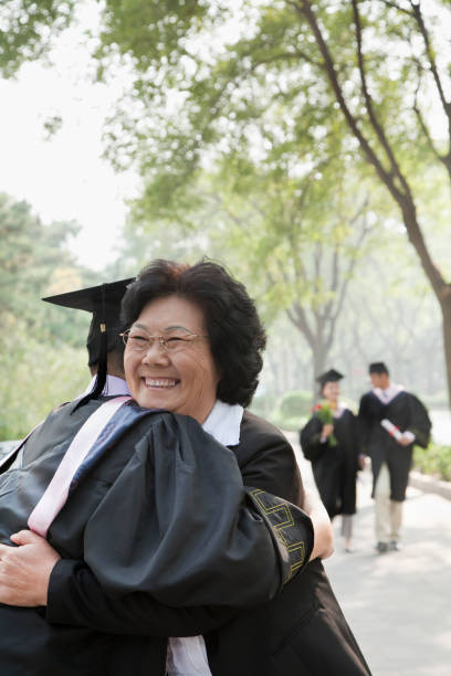 Chinese mother with student in graduation cap and gown Chinese mother with student in graduation cap and gown old mother son asian stock pictures, royalty-free photos & images