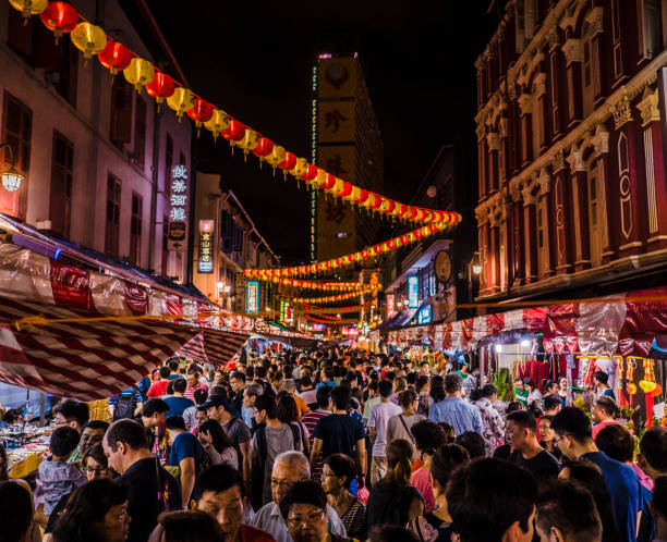 Chinese New Year Chinatown Singapore Crowd walking in the streets of Chinatown during the Chinese New Year celebrations in Singapore. Many people celebrate, eat and buy at the many market stalls that open till late at night during this popular celebration. night market stock pictures, royalty-free photos & images